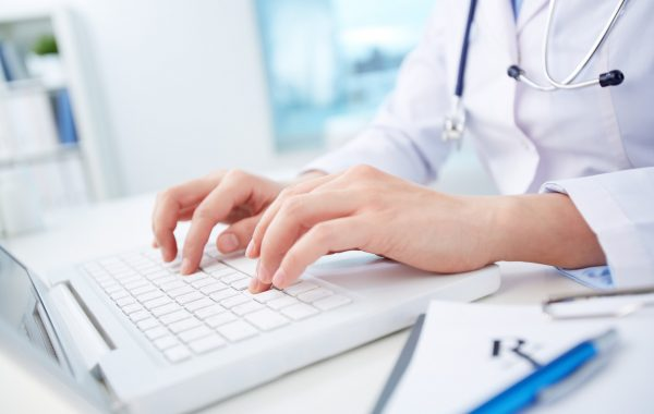 Close shot of a female doctor studying medical records via laptop